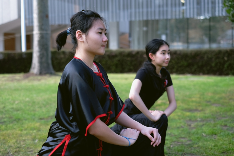 Members of Melbourne University Wushu and Taichi Club warm up before the class