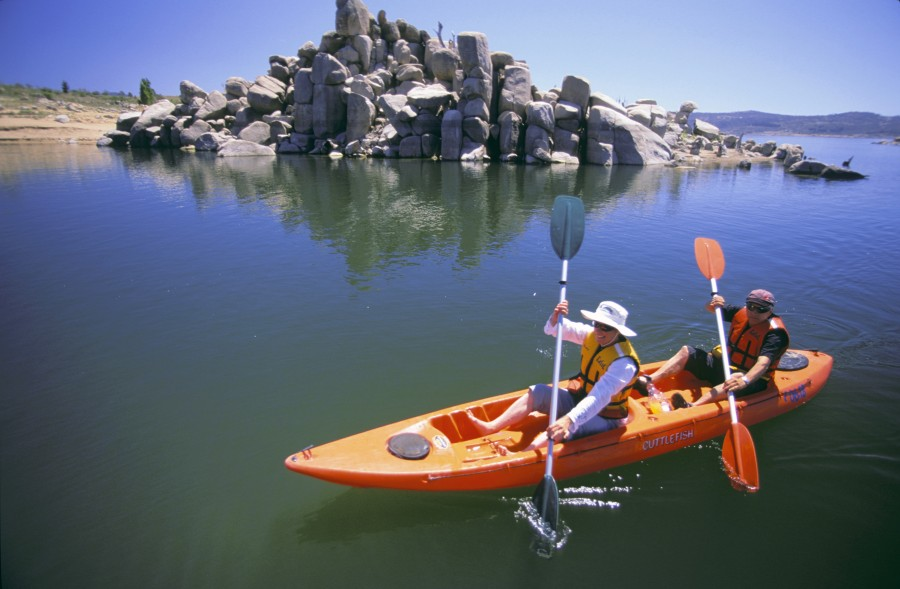 Destination-NSW-Two-people-paddling-in-a-kayak-on-Lake-Jindabyne-with-landrock-formation-in-background-Snowy-Mountains